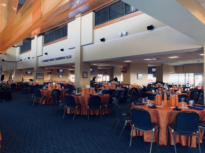 University of Florida Champions Club. There are many tables and chairs with orange and blue tablecloths, napkins, and dinnerware.